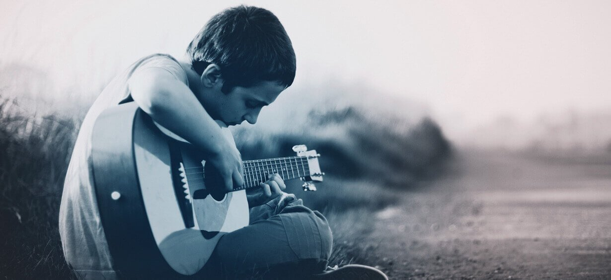 Boy sitting and playing guitar by an empty road
