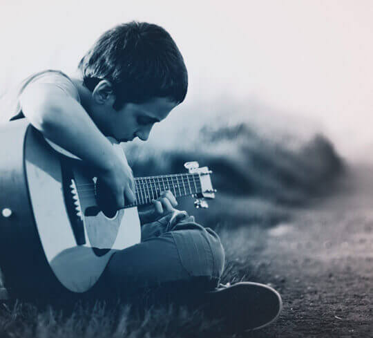 Boy sitting and playing guitar by the road