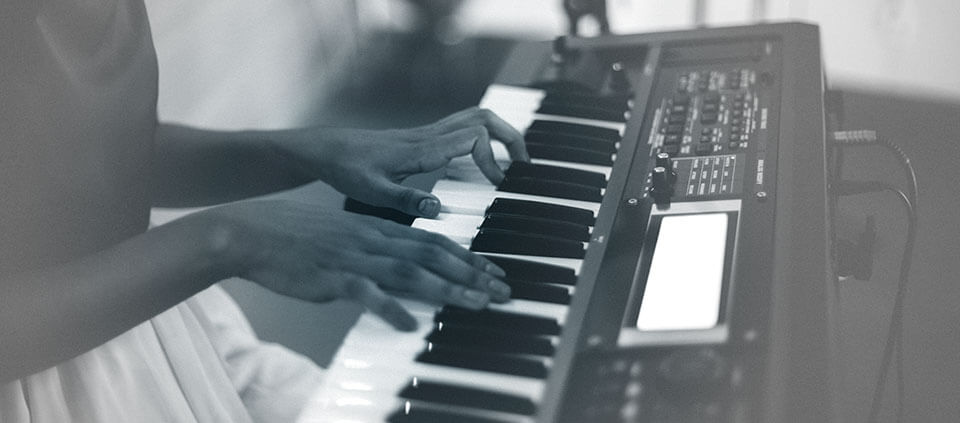 A girl's hands playing a synthesizer keyboard