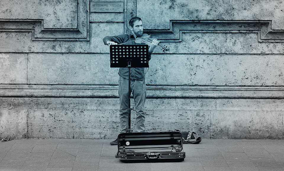Photo of man standing by himself and playing his violin, with a music stand, and his violin case on the ground, and some sort of cool-looking building behind him