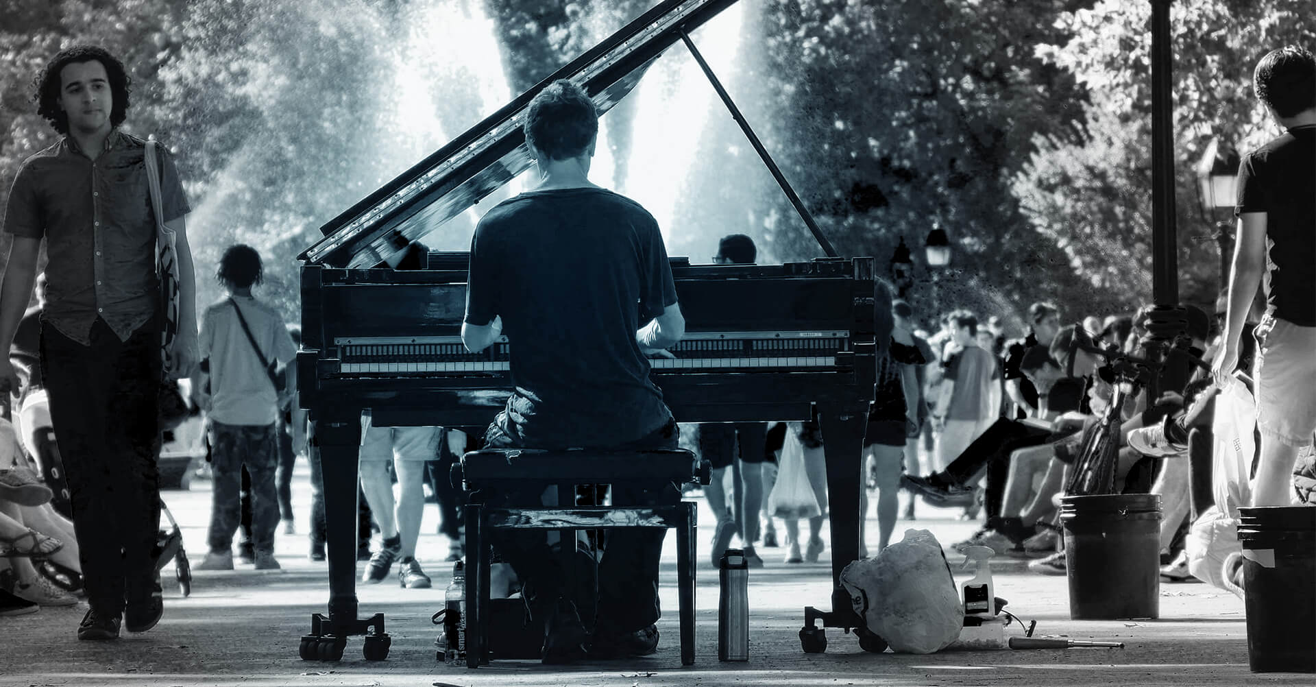 Feature image - man sits and plays grand piano in middle of a busy walkway with people all around